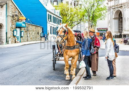 Quebec City Canada - May 29 2017: Old town street with view of hotel Chateau Frontenac and tour guide talking to tourists
