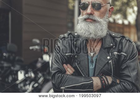 Confident bearded mature biker wearing leather jacket is standing afore motorcycle and crossing hands. Portrait. Copy space on left side