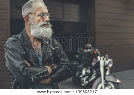 Assured elder bearded spectacled biker wearing jacket made of leather is standing afore garage and crossing hands. Copy space on right side