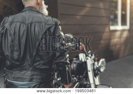 Old bearded biker is going to his vehicle. He wearing leather jacket. Focus on male back. Copy space on right side