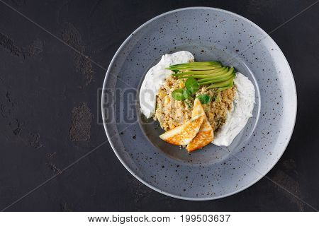 Healthy gourmet restaurant lunch. Quinoa salad with avocado, cucumber, halloumi cheese and tsadziki sauce in gray plate on black background. Traditional greek cuisine. Top view, copy space