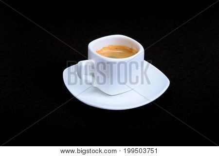 White cup of classic espresso coffee and pralines on black background