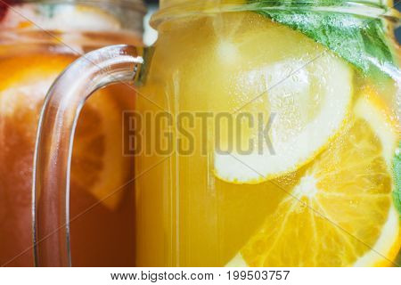 Background of fresh cold cocktails in jars. Close up picture of glass wall of fruit drinks with drops of water, sliced orange shape and mint, refreshment and coolness concept