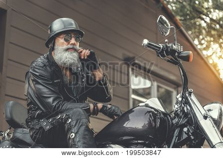Serious mature bearded biker wearing slam is sitting on motorcycle. He touching his moustache and looking ahead. Low angle. Portrait
