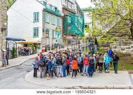 Quebec City Canada - May 29 2017: Tour group with young school children walking on old town street called Saint-Jean