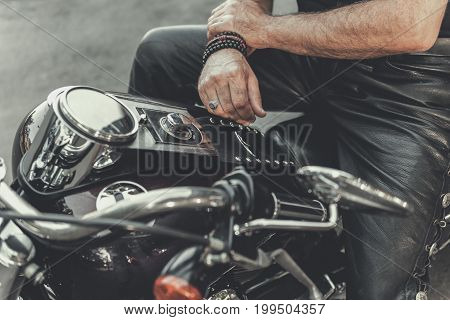 Biker is sitting at motorcycle. Focus on male hands near polished fuel tank. Mirror affixed to handle. Close up