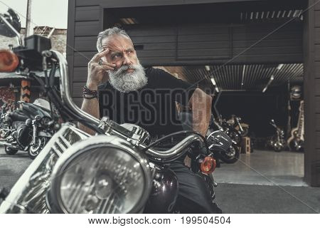 Mindful old bearded biker is sitting on motorcycle. He touching to face and looking aside with wistfulness. Portrait