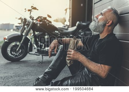 Thoughtful bearded elder biker is sitting near wall and holding alcohol. He looking up with bewilderment