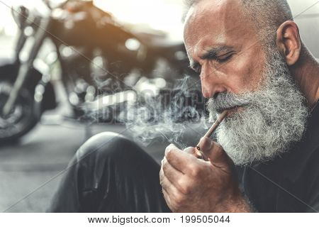 Concentrated aged biker is sitting near wall and setting fire to cigar. Focus on smoking bearded male person