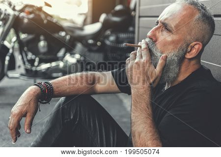 Relaxed elder biker is sitting near wall and using cigar. He locating beside his motorbike. Portrait