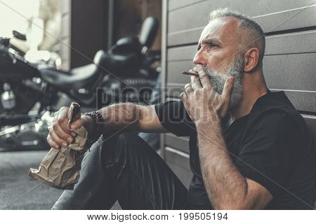 Mindful elder bearded biker is sitting near wall. He holding alcohol and smoking cigar. Man glancing ahead with weariness