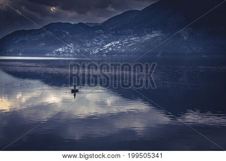 Idyllic mountains landscape with man in fishing boat in the middle of tranquil lake with water reflections during sunrise with dramatic sky in blue toned colors