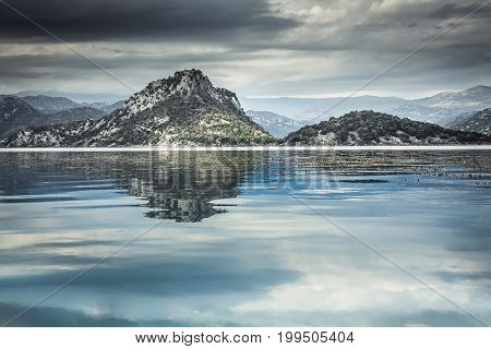 Tranquil lake water  with sky reflection and mountains  landscape in overcast day with dramatic sky in Europe country Montenegro at Skadar lake
