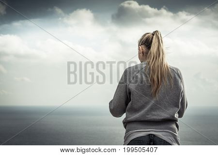 Pensive lonely woman looking with hope at horizon with bright sunlight in dramatic sky with effect of light at the end of tunnel