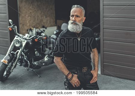 Concentrated mature bearded biker is standing afore motorbike. He putting arms in pockets and looking aside with wistfulness. Portrait