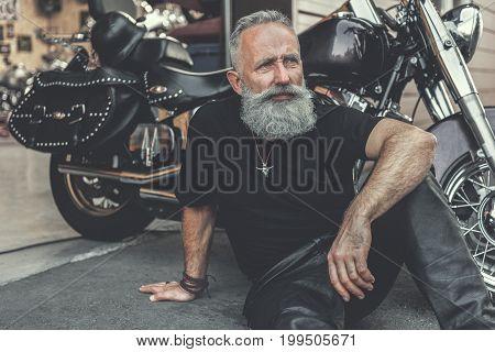 Thoughtful elder biker is sitting nearby motorbike. He looking ahead with wistfulness. Portrait