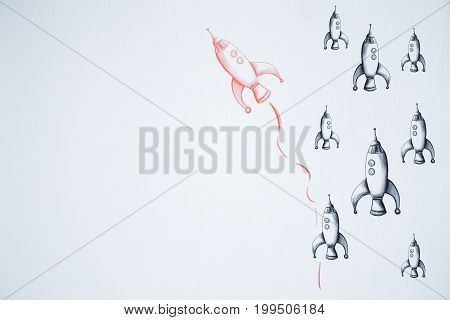 Think differently. Different drawn rocket ship on white wall background. Success concept