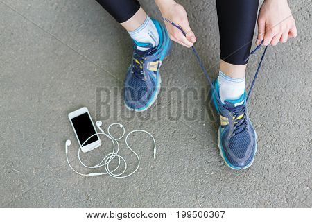 Woman tying shoes laces before running, getting ready for jogging in park, top view