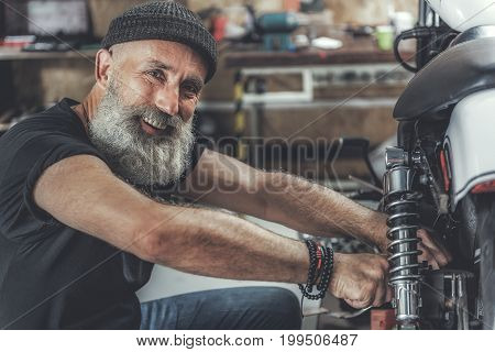Happy bearded old biker repairing his vehicle and looking at camera with wide smile. Garage is place for working. Portrait