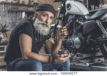 Mindful aged biker is smoking in garage near motorcycle. He using piston as ashtray and looking at camera with wistfulness. Portrait