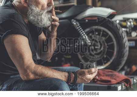 Mature biker is sitting near motorbike in garage and smoking cigarette. He holding piston as ashtray. Focus on male