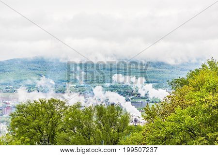 Industrial smoke or steam during cloudy fog mist and mountains over cityscape of Quebec City