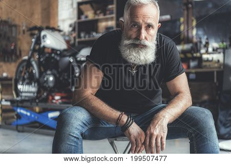 Serious bearded aged biker is sitting on chair and looking at camera with assurance. Portrait. Copy space on left side