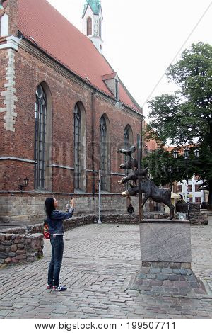 Riga Litva July 31 2017 Woman make photo on mobile phone Statue of the Bremen musicians