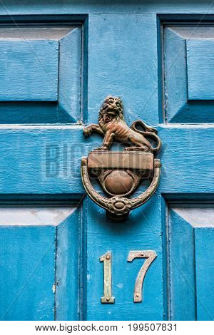 Closeup Of Blue Painted Wooden Door With The Number 17 And Lion Knocker Handle