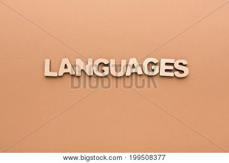 Word Language made of English letters on beige background, copy space. English language learning concept.