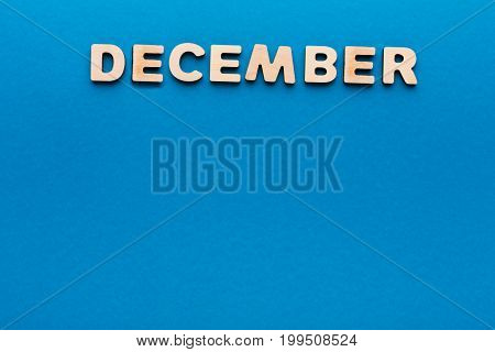 Word December made of wooden letters on blue background.Month planning, timetable concept