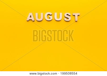 Word August made of wooden letters on yellow background. Month planning, timetable concept