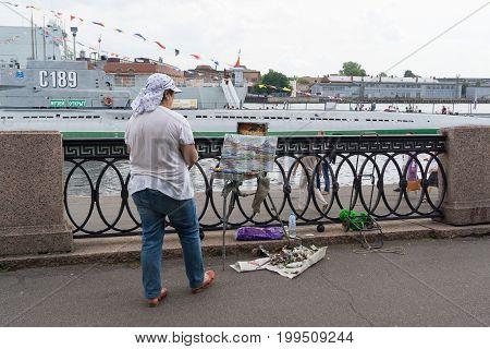 Saint Petersburg, Russia - July 29, 2017: an artist on the Neva river draws a warship