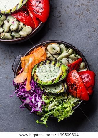 Budha Bowl. Raw Vegetables With Beans, Grilled Avocado And Bell Pepper On Slate Background. Top View
