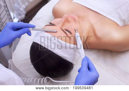 The physician-cosmetologist makes Electric Facial Treatment of the skin of a beautiful young woman in a beauty salon. Cosmetology and professional skin care. poster