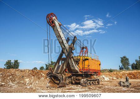 Big industrial orange quarry excavator on construction site, quarry equipment