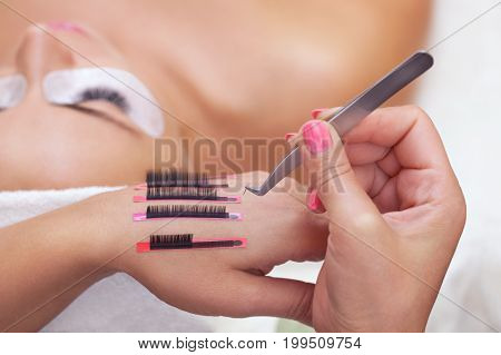 The procedure for eyelash extensions in the beauty salon eyelashes on the hand of the make-up artist. In the background a girl with long eyelashes.