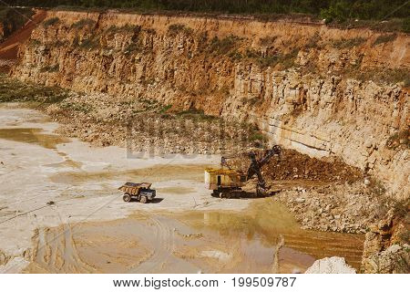 Quarry truck and quarry excavator machine works in limestone mining sand and clay quarry in Eletz, Russia