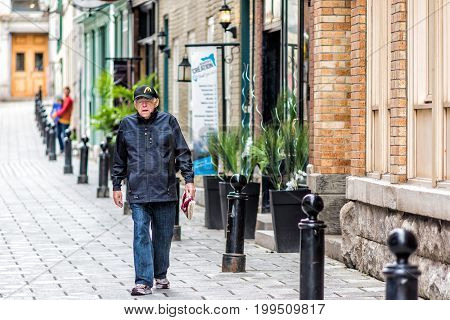 Quebec City Canada - May 30 2017: Lower old town street called Rue du Sault-au-Matelot with closeup of older senior local man walking on cobblestone
