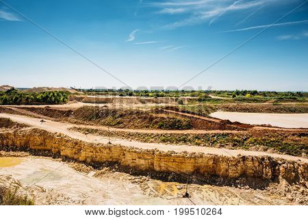 Sand and clay quarry mining landscape, yellow and orange rocks and blue sky