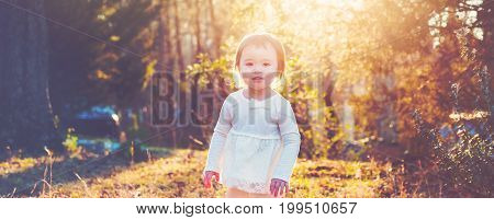 Happy toddler girl playing outside at sunset