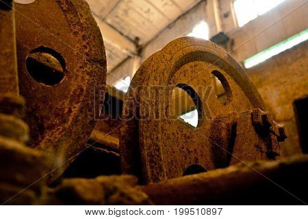 Close up view of old rusty pulleys in an abandoned factory