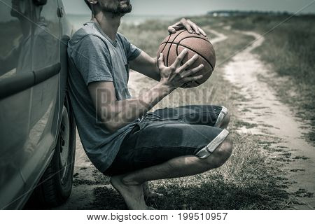 young man with basketball ball on the road the emotions of the athlete the concept of sport