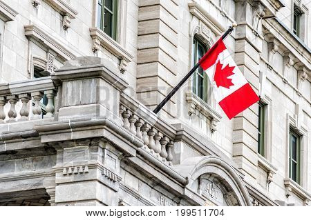 Quebec City Canada - May 30 2017: Red Canadian flag with maple leaf hanging on stone building by old town street