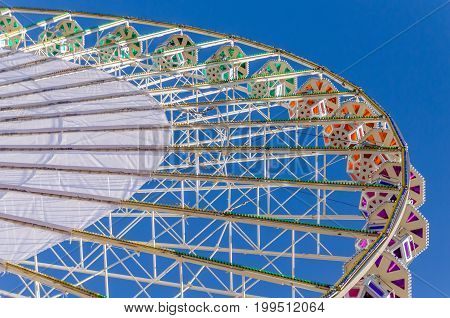Ferris wheel with colored cabins against a clear blue sky at a funfair in Lyon