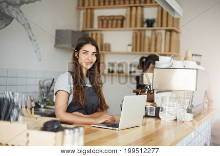 Barista lady waiting for a customer coffee order, starting a day on her dream job.