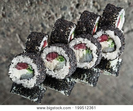Black roll made with tuna, scallop, cucumber over concrete background