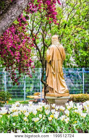 Quebec City Canada - May 30 2017: View of Seminary golden statue of Jesus Christ and white tulips in garden