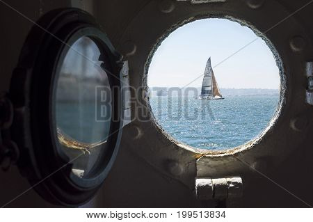 SAN DIEGO CALIFORNIA USA - AUGUST 9 2017: Stars and Stripes USA-11 the America's Cup racing yacht sailed by Dennis Conner can be seen through a port hole in the famous Star of India ship giving tours on San Diego Bay.