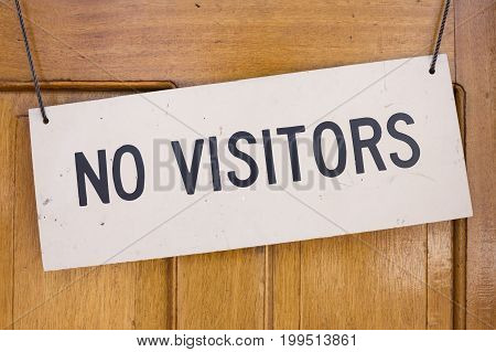 Closeup of No Visitors sign placard hanging on wooden door